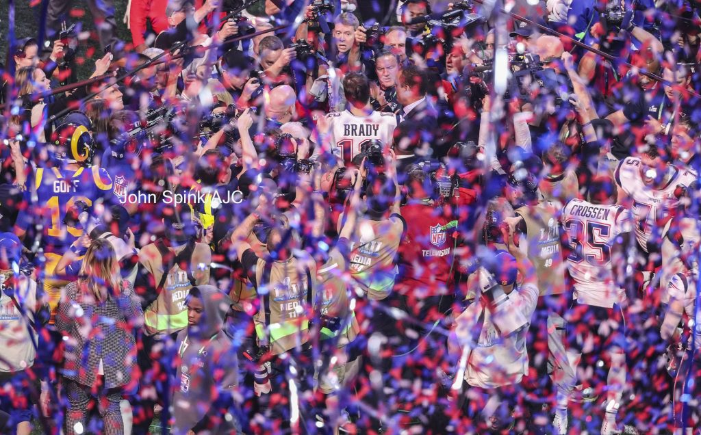 John Spink/Atlanta Journal-Constitution - Los Angeles Rams quarterback Jared Goff (left) tries to make his way to New England Patriots quarterback Tom Brady (right) in a shower of confetti.