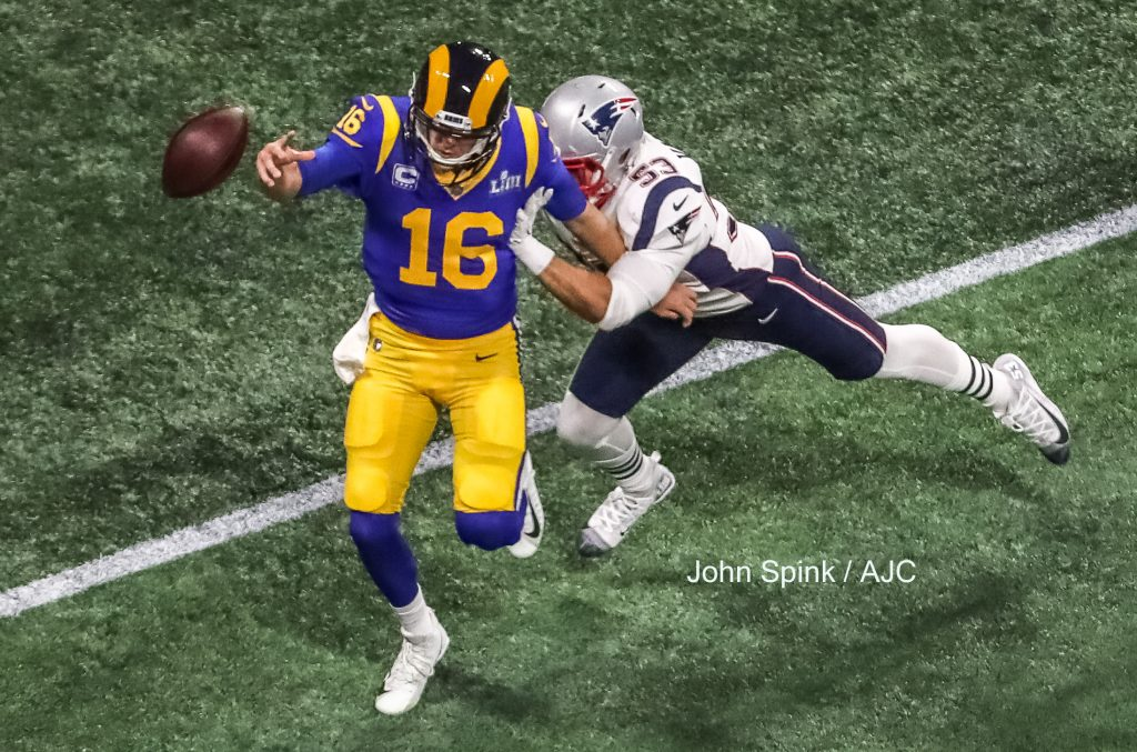 John Spink/Atlanta Journal-Constitution - Los Angeles Rams quarterback Jared Goff (16) throws the ball away after pressure from New England Patriots middle linebacker Kyle Van Noy (53).